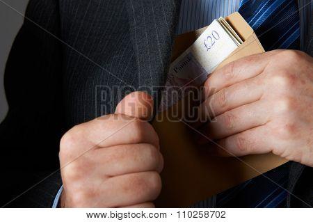 Businessman Putting Envelope Of Sterline Notes In Jacket Pocket