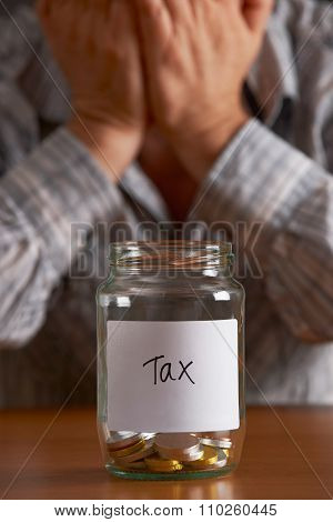Man With Head In Hands Looking At Jar Labelled Tax