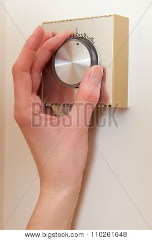 Close Up Of Woman Adjusting Central Heating Thermostat Control