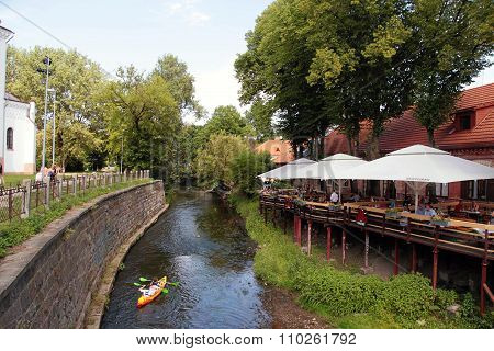 Cafe Terrace And Canoe Boat In River Vilnele Near Uzupis Neighborhood, Vilnius, Lithuania.