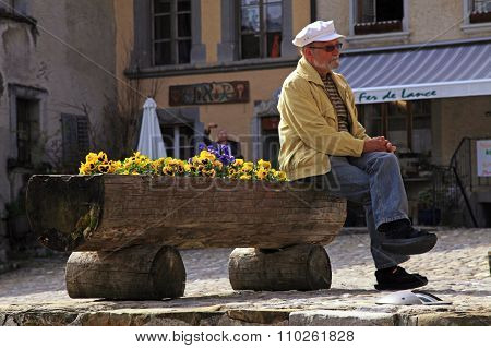 Senior Man Sitting In The Swiss Village Gruyeres, Switzerland.