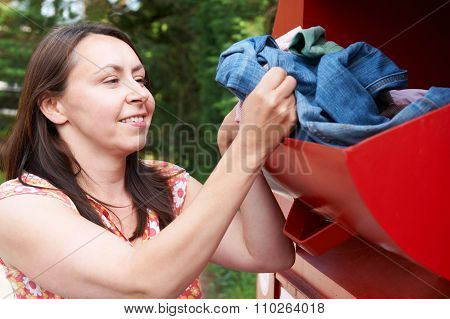 Woman Putting Old Clothes Into Recycling Bank
