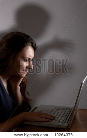 Teenage Girl Using Laptop With Menacing Shadow In Background