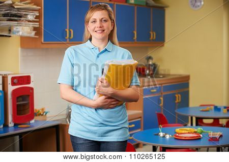 Childcare Worker Standing In Nursery