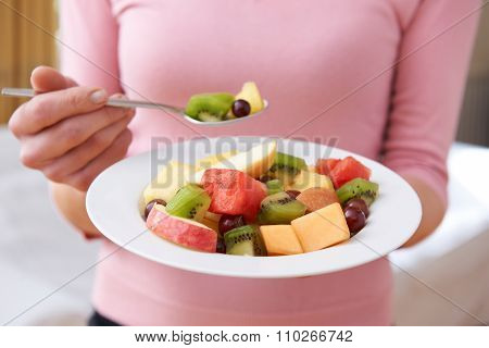 Close Up Of Woman Holding Bowl Of Fresh Fruit