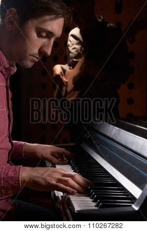 Musicians Playing Electric Piano And Bass Guitar In Recording St