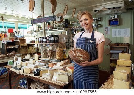 Owner Of Delicatessen Standing In Shop Holding Loaf