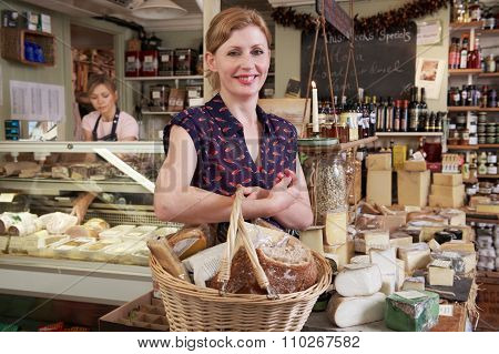 Woman Carrying Basket Of Groceries In Delicatessen