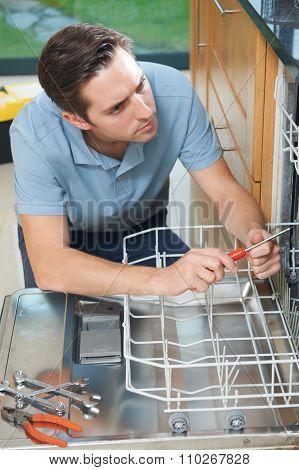 Man Repairing Domestic Dishwasher In Kitchen