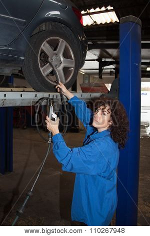 Woman As Female Car Mechanic Working On An Auto In Workstation