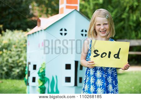 Little Girl Holding Sold Sign Outside Cardboard Playhouse