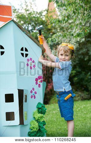 Young Boy Pretending To Fix Cardboard Playhouse