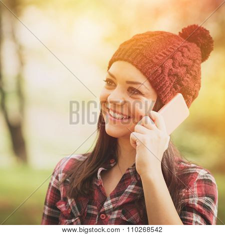 Happy young woman in knitted hat talking on smartphone