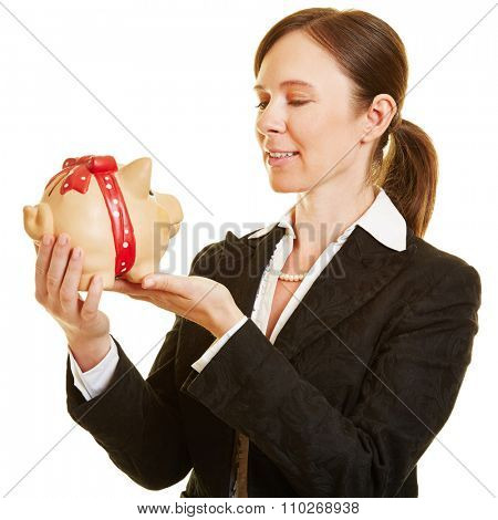 Smiling businesswoman looking at her piggy bank