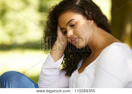 Depressed Young Woman Sitting Outdoors