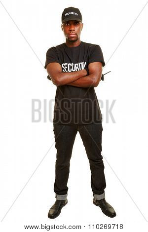 Black security guard with radio set holding his arms crossed