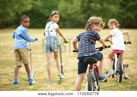 Happy children with bikes and scooter in nature