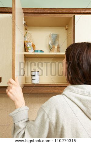 Woman Looking In Empty Food Cupboards