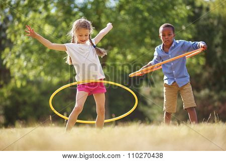 Girl and boy with hula hoop playing at the park