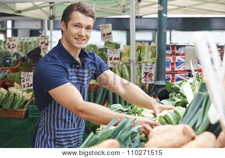 Man Arranging Display On Market Vegetable Stall
