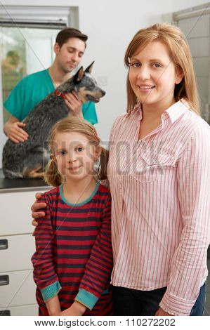 Mother And Daughter Taking Dog For Examination At Vets