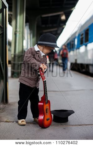 Boy With A Guitar On A Railway Station