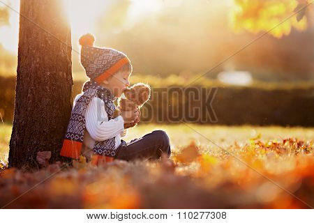 Adorable Little Boy With Teddy Bear In Park On Autumn Day