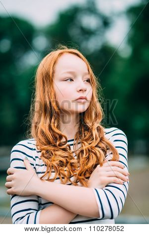 Outdoor Portrait Of Pretty Red-haired Girl With Green Eyes Who Hugging Herself. Adorable Young Redhe