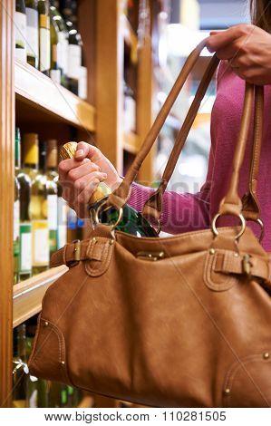 Woman Stealing Bottle Of Wine From Shop