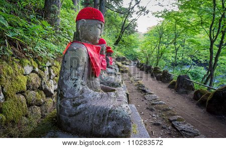 Wide angle of statues in Nikko with track