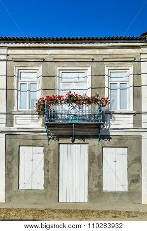 Simple Balcony Of A One-story House, With Well Maintained  Old House, With White Windows And Door, A