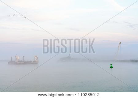 Lake Boat Engulfed With Fog. Horizontal View Of A Commercial Boat Leaving The Harbor, Early In The M