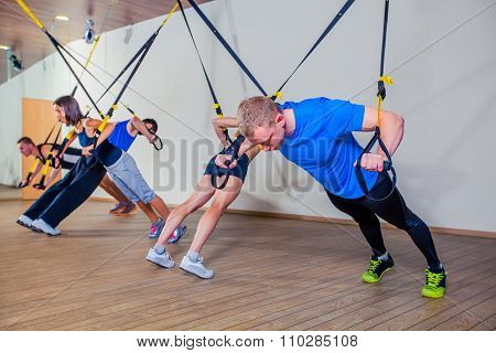 People make fitnes exercise with a band in the gym. TRX
