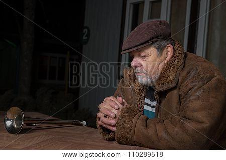 Portrait of senior man sitting next to his house