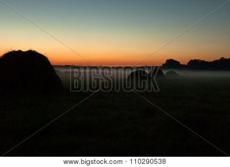 Dense Evening  Fog Over The Meadow And Haystacks Just After Sunset In Summer.horizontal.