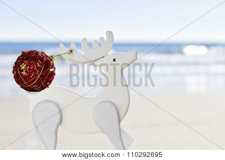 closeup of a red christmas ball in the antler of a white wooden reindeer, with the sea in the background