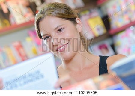 Lady in newsagents holding a book