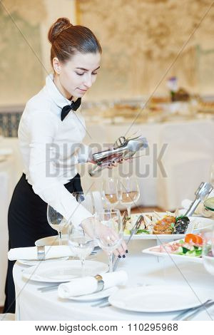 waitress occupation. Young woman with food on dishes servicing in restaurant during catering the event