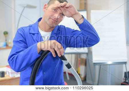 Male office cleaner wiping his brow