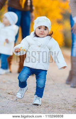 Little girl in yellow autumn park