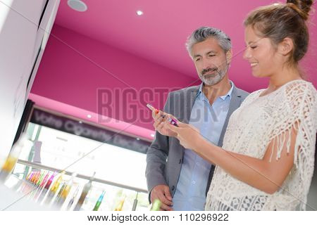 Shop assistant showing vaporiser to customer