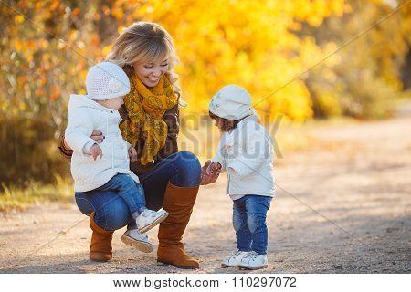 Happy mother with children in autumn park