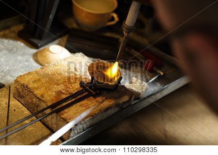 Jeweler melting precious metal