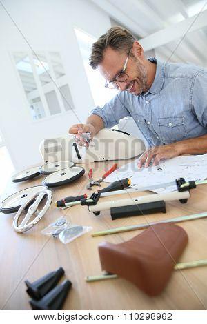 Man at home assembling toy car parts