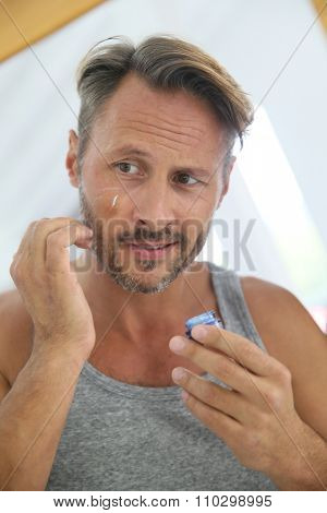 Handsome man applying anti-wrinkle cream on his face