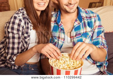 Happy Loving Couple Eating Popcorn On The Couch