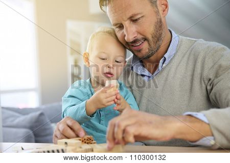 Daddy with 2-year-old boy playing with wooden blocks
