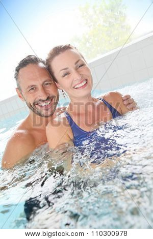 Couple enjoying hot tub bath in spa center