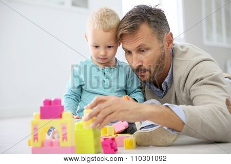 Daddy with baby boy playing with blocks on the floor