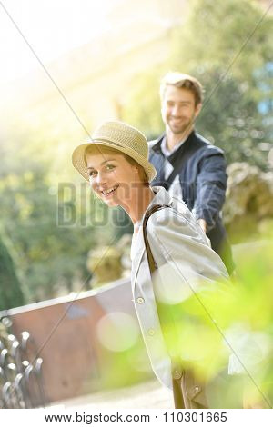 Woman walking in park, pulling boyfriend's arm